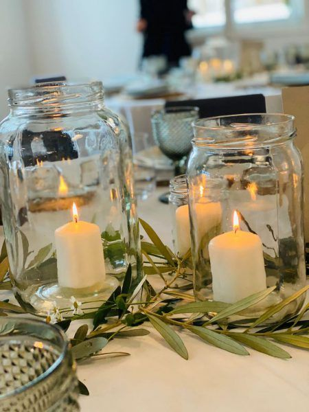 Centros de mesa con botes de cristal, veloncitos, ramas de olivo y florecitas de manzanilla.