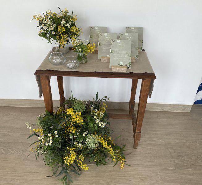 Mesa con flores, tarros de cristal con velas y tarjetones